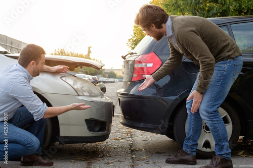 Two men arguing after a car accident on the road Poster