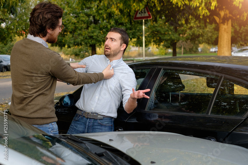 Two men arguing after a car accident on the road Canvas Print