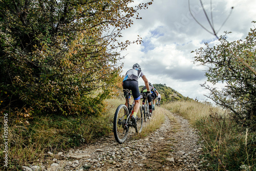 Photo sur Toile Cyclisme group of cyclists on sports mountainbike riding uphill. Cycling competition