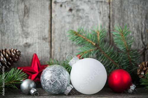 Foto  Red, silver and white xmas ornaments on rustic wood background