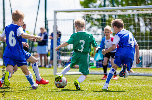 Football soccer match for children. Boys playing football game on a school tournament. Dynamic, action picture of kids competition during playing football. Sport background image.