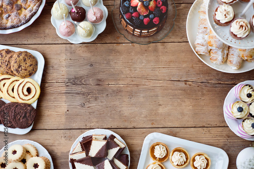 Photo  Table with cake, pie, cupcakes, tarts and cakepops. Copy space.