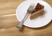 A Slice Of Toffee And Chocolate Cheesecake Dessert On A Wooden Background
