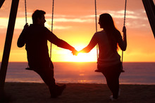 Couple Silhouette Holding Hands Watching A Sunrise