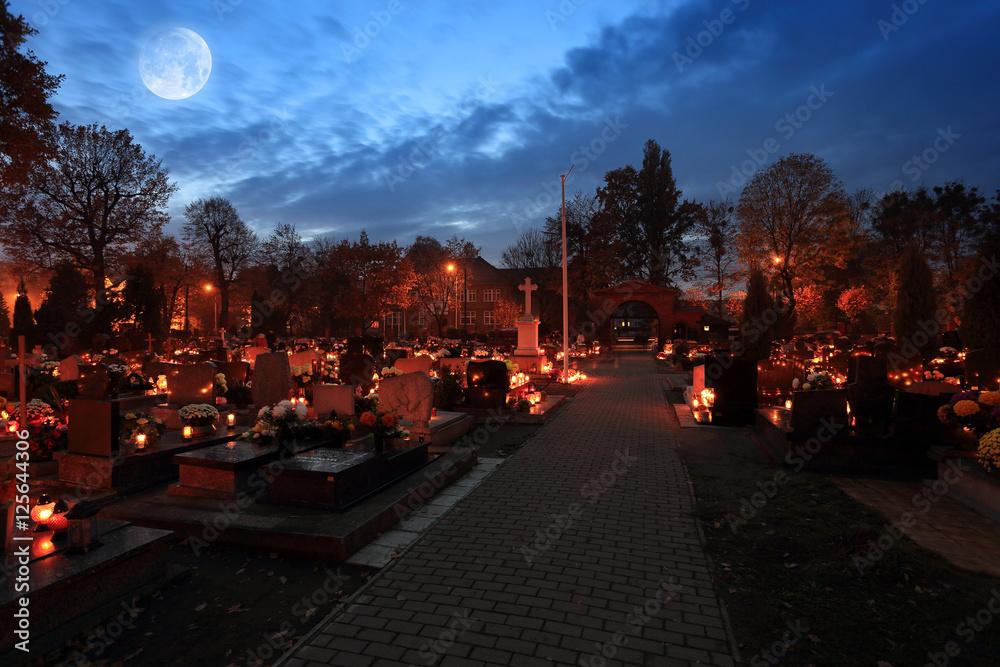 Fototapeta Cmentarz nocą z kolorowymi świecami w Dniu Wszystkich Świętych, księżyc.