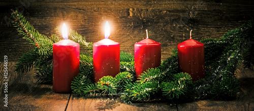 Zweiter Advent: zwei leuchtende Kerzen vor einem Holzhintergund Tableau sur Toile