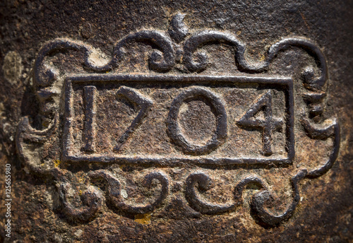Fotografie, Obraz  year 1704 carved on a rusty iron surface
