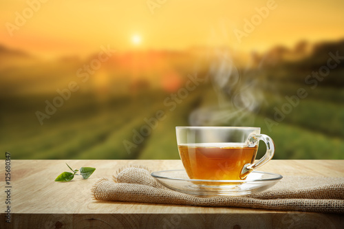 Valokuva Cup of hot tea and tea leaf on the wooden table and the tea plantations backgrou