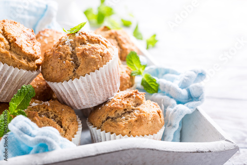 Fotografie, Obraz  Delicious homemade coconut cinnamon muffins and mint leafs on old white tray