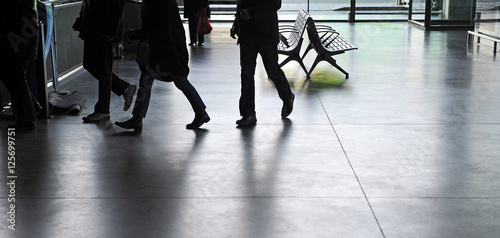 Silhouettes of people walking backlit