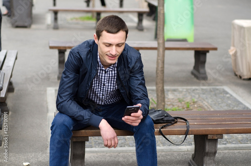 Fototapety, obrazy: Young man using his phone