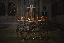 Burning Candles Near Cross With Calvary In Georgian Samtavro Church