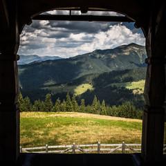 Fototapeta A beautiful Carpathian scenery through an arc of a window