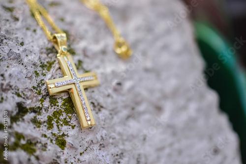 Zdjęcie XXL Złoty chrześcijanina krzyż na kamiennej ławce
