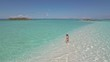 Woman walking on tropical beach. Exuma, Bahamas.