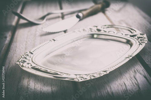 Fotografia, Obraz Vintage pewter plate, fork and knife on old dark wooden board