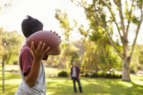 Fotomural Young boy throwing ball to dad in park, focus on foreground