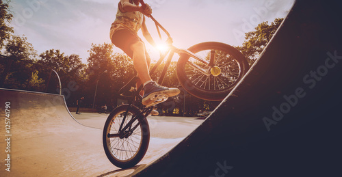 Boy riding a bmx in a park.