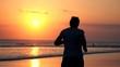 Man jogging on beach during sunset, super slow motion 240fps