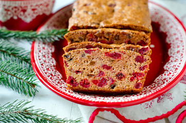 Traditional Christmas cake with dried fruits on a red plate