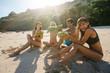 Friends enjoying beach vacation with fresh coconut drink