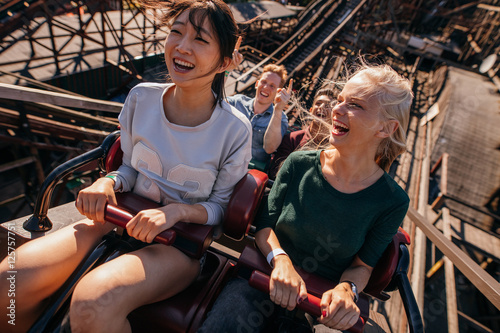 Poster Attraction parc Smiling young people riding a roller coaster