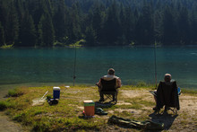 Two Fisherman Sitting On A Chair And Catch A Fish, Dobbiaco Lake, Italy