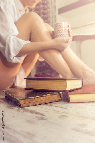 Deurstickers Ontspanning woman reading a book and drinking coffee in her comfortable home