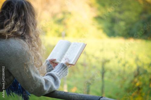 Deurstickers Ragazza con maglione si rilassa leggendo un libro al parco in autunno