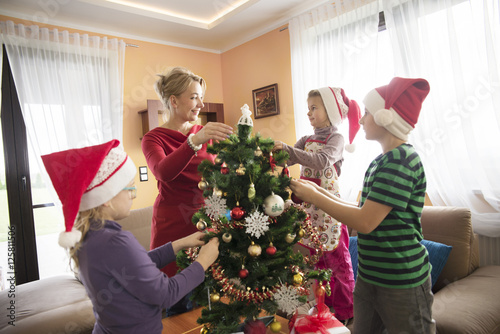 Fényképezés  Mum putting on christmas decorations on a christmas tree with her kids