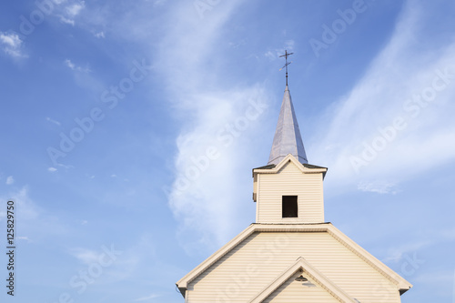 Country church steeple against blue sky and white clouds