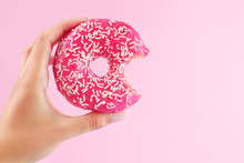 Female Hand Holding Delicious Donut On Pink Background, Closeup