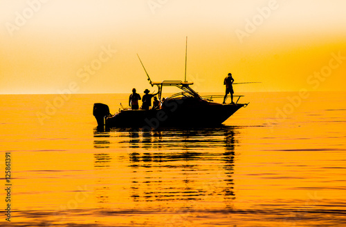 Valokuva silhouette of sport fishing boat reflecting on calm water