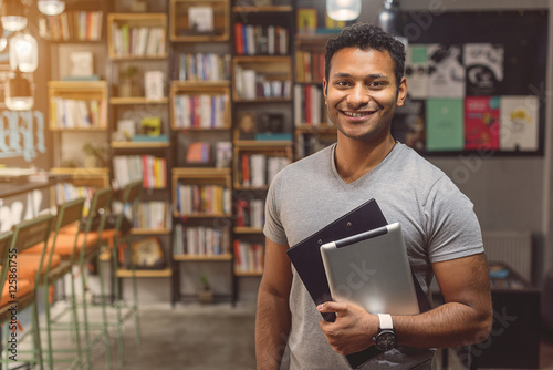 Valokuva  African man standing in campus library