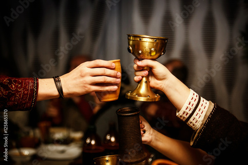 Photo people clink cups on a medieval feast.