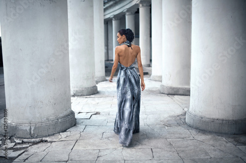 Photo  young lady in dress at the entrance of neoclassical building