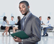 african american businessman in modern office with colleagues on background