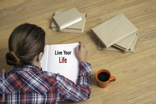 Fotografie, Obraz  Woman reading book Live Your Life by stack of books