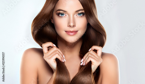 eautiful model girl with shiny brown straight long  hair . Care and hair products .