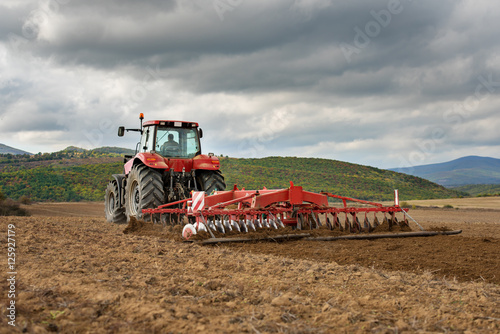 Fényképezés  Farmer in tractor preparing land with seedbed cultivator