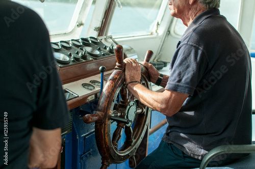 Capitan de barco manejando el timon Wallpaper Mural