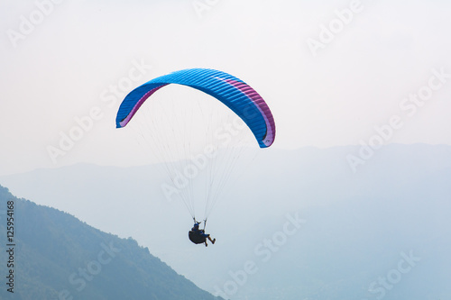 Foto op Plexiglas Luchtsport Paraglider flight over the mountains