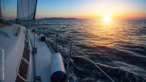 Fotografie, Tablou  Sailing boat in the sea during a beautiful sunset.