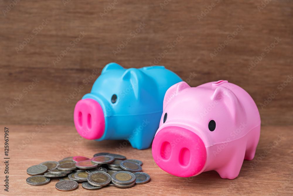 Photo & Art Print plastic blue and pink piggy bank with coins on