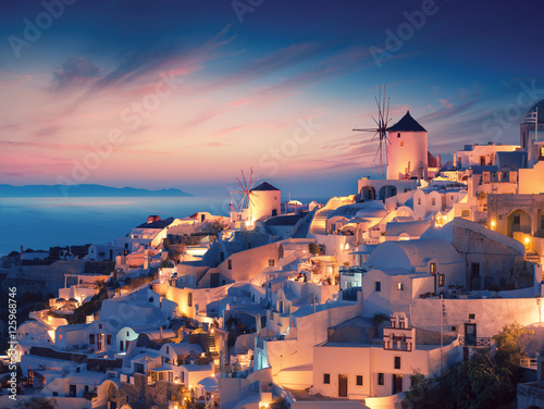 Amazing sunset view with white houses in Oia village on Santorini island in Greece. Wall mural