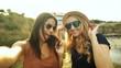 Two beautiful girls taking selfies.