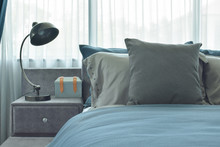 Gray And Deep Blue Pillows Setting On Bed With Industrial Style Reading Lamp Next To Bed