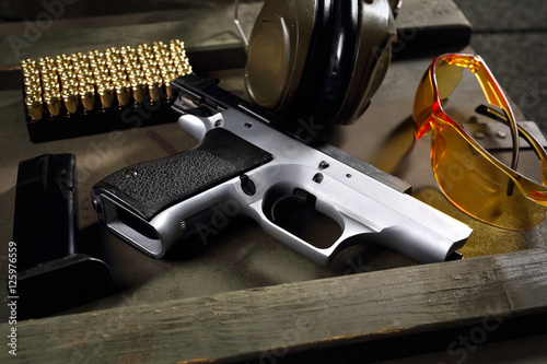 Obraz Pistolet CZ Shadow. Pistolet Cz, naboje i słuchawki ochraniające uszy, sprzęt strzelecki - fototapety do salonu
