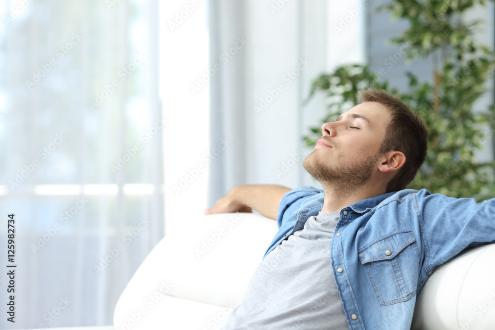 Fototapeta Man resting on a couch at home