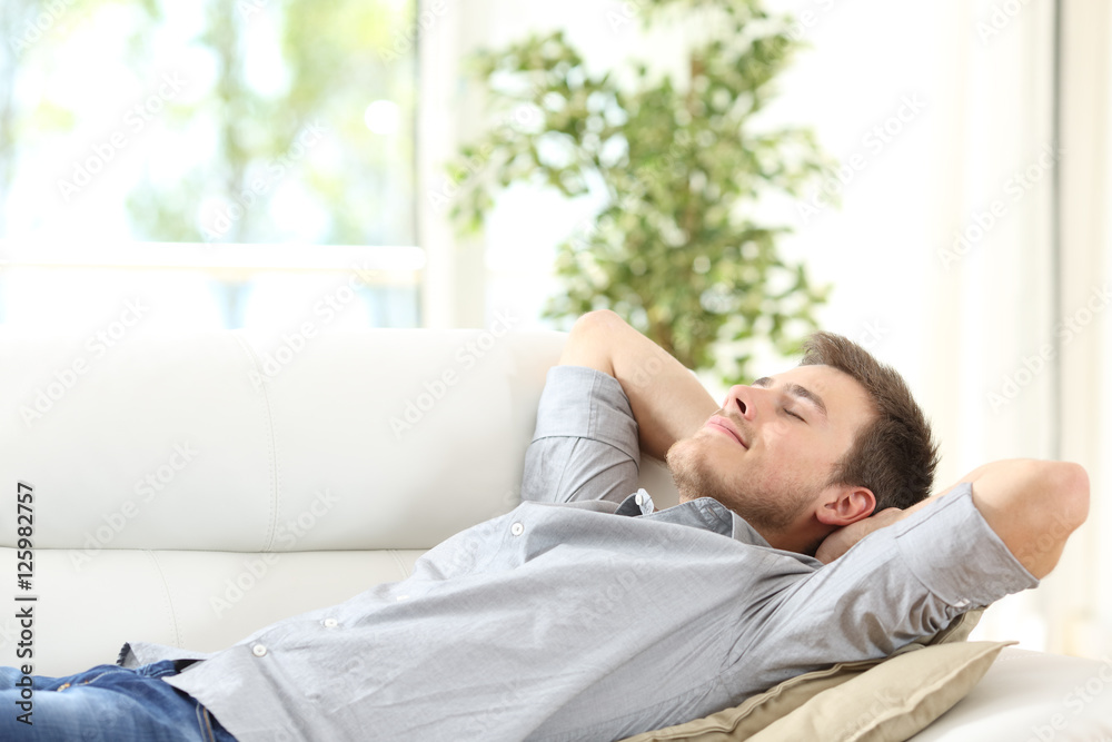 Fototapeta Relaxed man resting on a couch at home